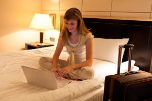 woman using laptop on her bed